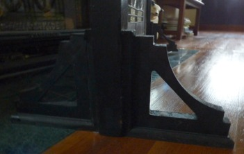 shelf brackets holding up stained glass window